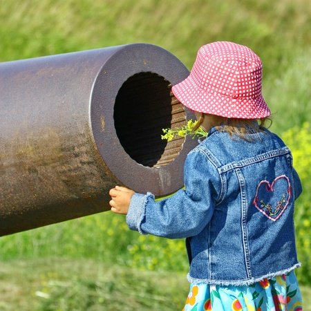 Little girl, gun and yellow flowers  Old Russian Cannon in Suomenlinna Sveaborg Helsinki Finland