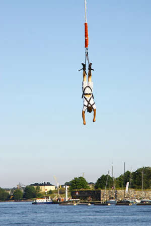 gained: HELSINKI, FINLAND - JULY 27: Bungee jumping from a crane on July 27, 2012 in Helsinki. The height of the jump is 150 metres, the speed gained during a jump is about 120 kmh