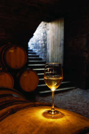 A glass of Chardonnay sits on a wine cask in the cellar at the Domain Chavy winery