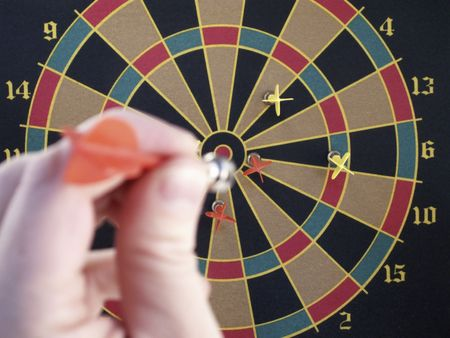 strive: Darts and bulls eye in focus as hand draws back to throw dart. Stock Photo