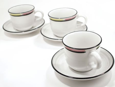Beverage cups with colorful rims, and saucers receede to upper left on white background. photo