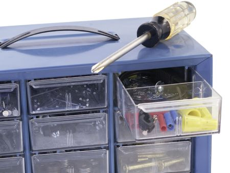 fixer: Screwdriver rests on top of hardware organizer box with one drawer open -- isolated on white background.