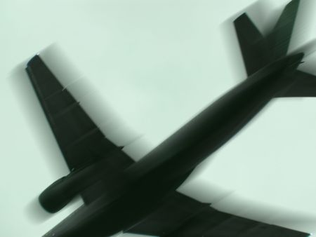 jetliner: Edgy shot of underbelly of jetliner in motion, overhead but low in green afternoon sky.