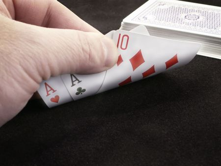 dealt: Close-up of hand of cards peeking at two aces and a ten.