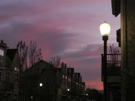 rowhouses: Brilliant mauve and purple sky backs silhouetted rowhouses with street lamp in foreground.