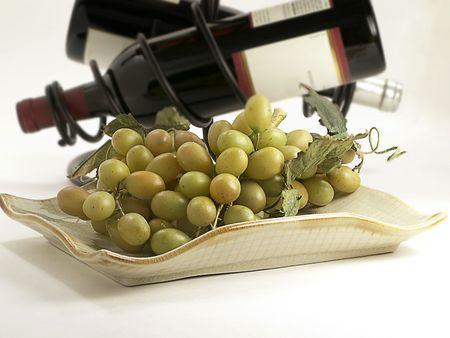 intoxicant: Green uve sito sul piatto di portata con le bottiglie di vino in rack dietro.