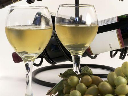 intoxicant: Close-up di vino in bicchieri con uve di fronte e bottiglie a indietro.