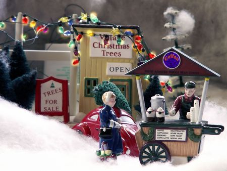 merchant: Coffee merchant and customer stand in front of Christmas Tree lot in decorative village. Stock Photo