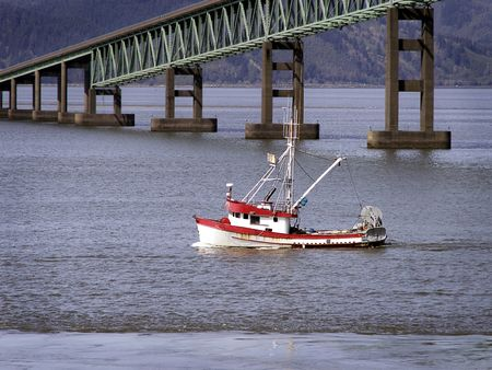 Red and white fishing trawler headed toward ocean, passing green river bridge. photo
