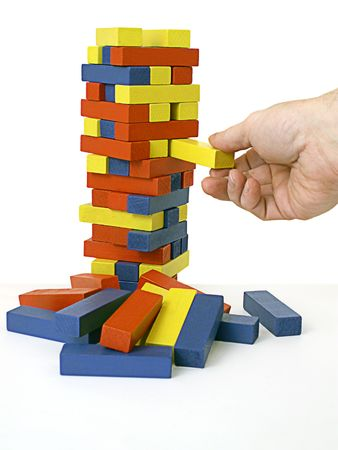 peril: Hand takes risk of removing one block from tower Stock Photo