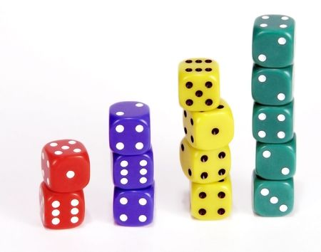 vertical bars: Stacks of dice form vertical bars of red, blue, yellow and green cubes, increasing in height. Stock Photo