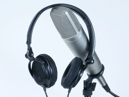 airwaves: Headphone headset rests on professional studio cardioid microphone on table stand, isolated against white backround.