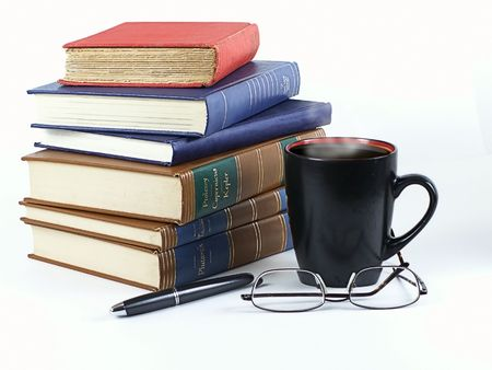 hardback: Stack of leather and hardback books with steaming coffee in mug, pen and glasses... ready to study.