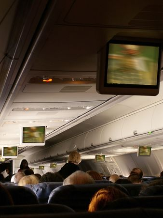 jetliner: Stewardess serves passengers aboard jetliner as move plays on overhead monitors in cabin.