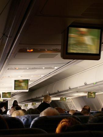 jetliner: Stewardess serves passengers aboard jetliner as move plays on overhead monitors in cabin.