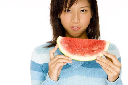 A serious looking girl holding slice of melon photo