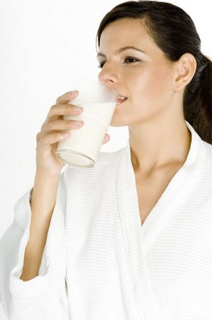 A beautiful young woman drinking from a glass of milk photo