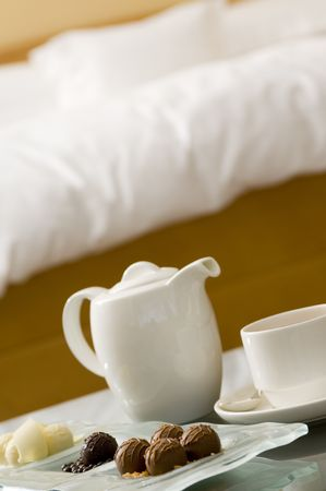 A plate of chocolates with tea set in front of bed (shallow depth of field used) photo