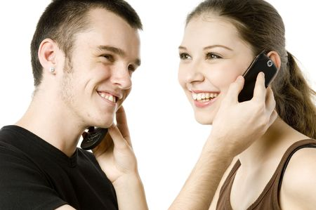 A young man and a young woman swapping phones on white background