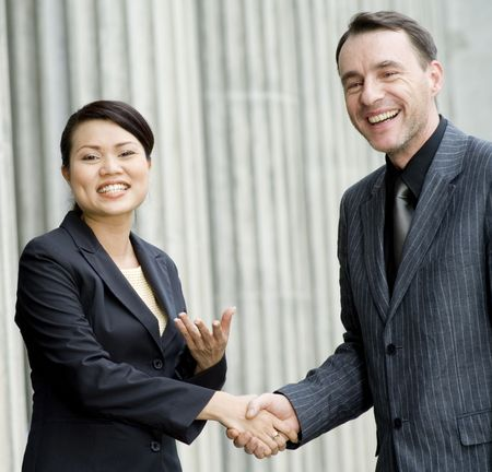 Two business people smiling and shaking hands Stock Photo - 893421