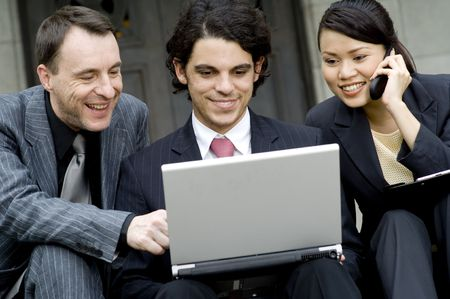 Three co-workers enjoying working on a laptop outside a building photo