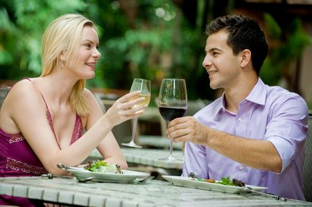 An attractive caucasian couple having a meal with wine at an outdoor restaurant photo