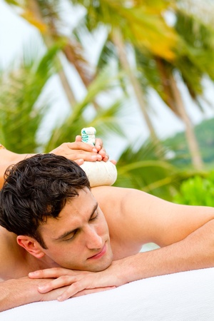 An attractive young man enjoying a back massage at a spa outdoors Stock Photo - 9804484