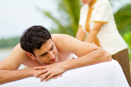An attractive young man enjoying a back massage at a spa outdoors Stock Photo - 9804486