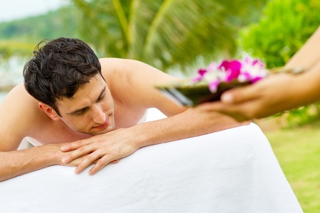 An attractive young man enjoying a back massage at a spa outdoors Stock Photo - 9804487