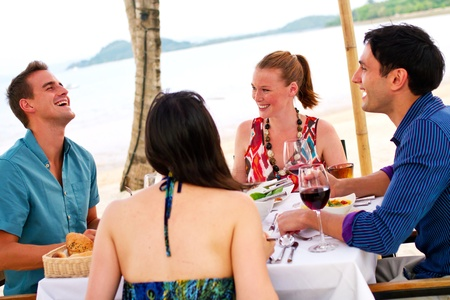 Four friends enjoying a meal by the beach. Stock Photo - 9804496