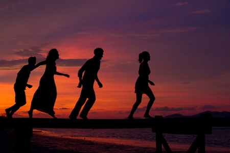 Four friends enjoying the sunset on a jetty Stock Photo - 9804482