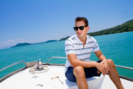 An attractive young man relaxing outdoors on a boat Stock Photo - 9804492