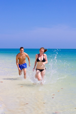 An attractive Asian couple running along the beach Stock Photo - 9804491