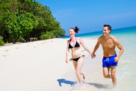 An attractive Asian couple running along the beach photo