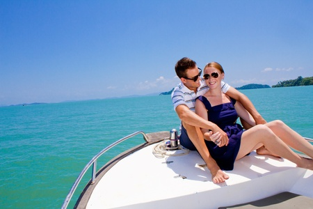 An attractive young couple relaxing outdoors together on a boat photo