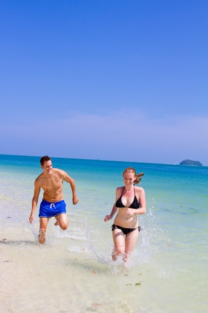 An attractive couple running along the beach Stock Photo - 9919164