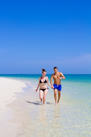 An attractive couple strolling along the beach Stock Photo - 9919157