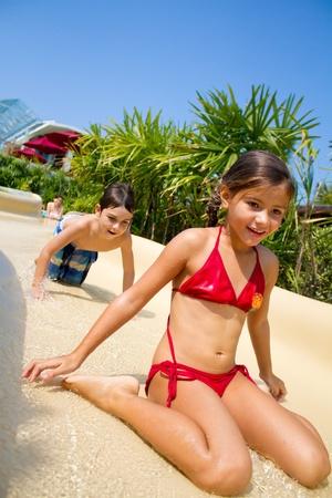 Junge Kinder schieben Sie die Wasserrutsche Standard-Bild