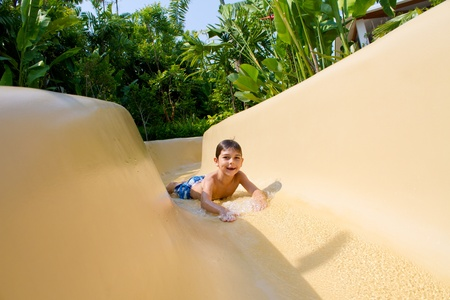 Young boy sliding down the water slide enjoying himself. Stock Photo - 9919190