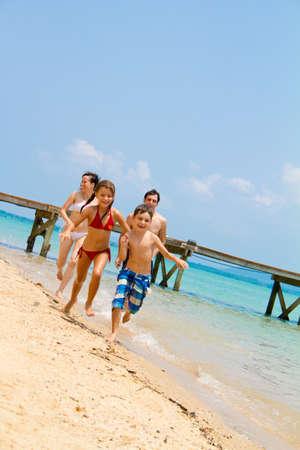 Junge und attraktive vierköpfige Familie amüsieren am Strand.