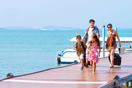vacation: A family of 4 arriving at the resort with their luggages. Stock Photo