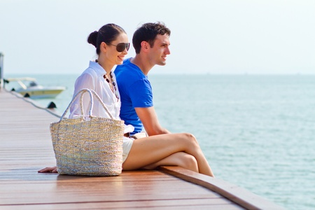 Side view of a couple sitting at the edge of a wooden boardwalk of a harbour Stock Photo - 10297184