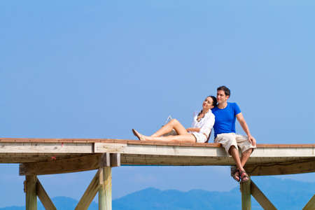 Front view of a couple sitting at the edge of a wooden boardwalk of a harbour Stock Photo
