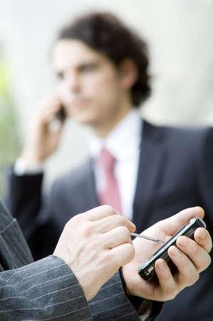 gente comunicandose: Gente que se comunica con diversos dispositivos m�viles (profundidad del campo baja usada)