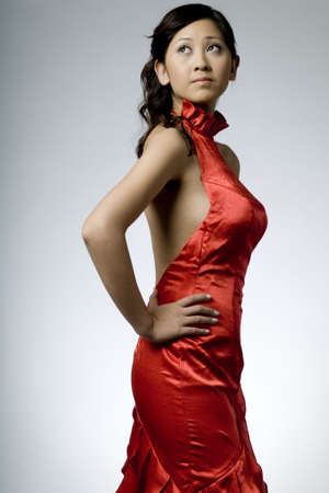 red evening: A beautiful asian woman in a red evening dress on grey background
