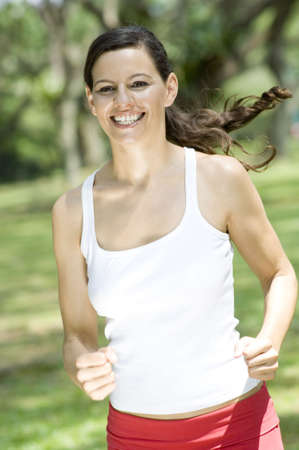 A young attractive sporty woman running in the sunshine outdoors Stock Photo