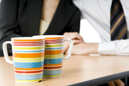 A pair of colorful coffee cups (in focus) with two business people holding hands in background