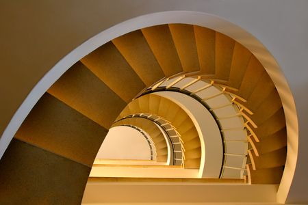 Spiral steps in a building with beautiful, warm lighting Stock Photo