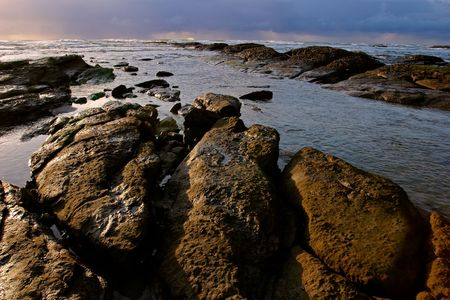 Seascape at sunrise with rocks in foreground  Stock Photo