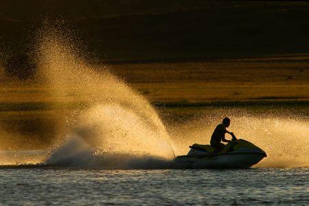 moto acuatica: Aerosol de agua retroiluminado del esqu� del jet, �ltima tarde